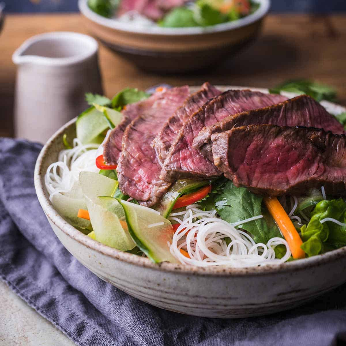 Vietnamese beef salad with thinly sliced steak in a bowl over a blue kitchen towel