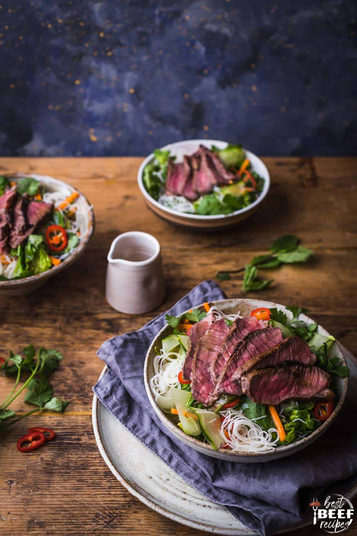 Three bowls of Vietnamese beef salad on a table with a small pitcher of salad dressing