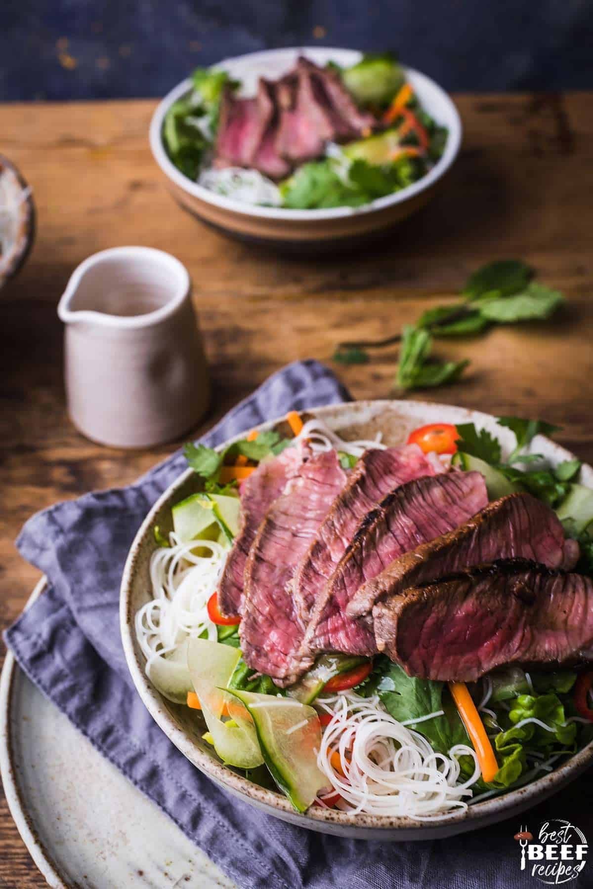 Two bowls of Vietnamese beef salad with a small pitcher of Asian salad dressing
