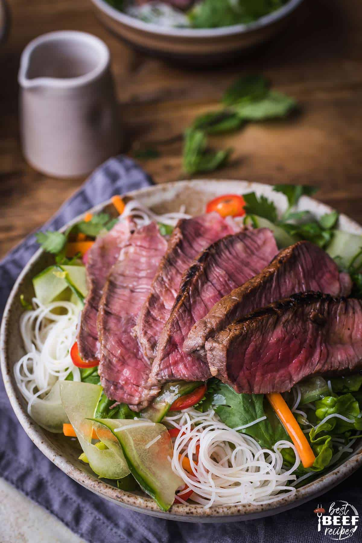 A bowl of steak salad with Vietnamese salad dressing and rice noodles