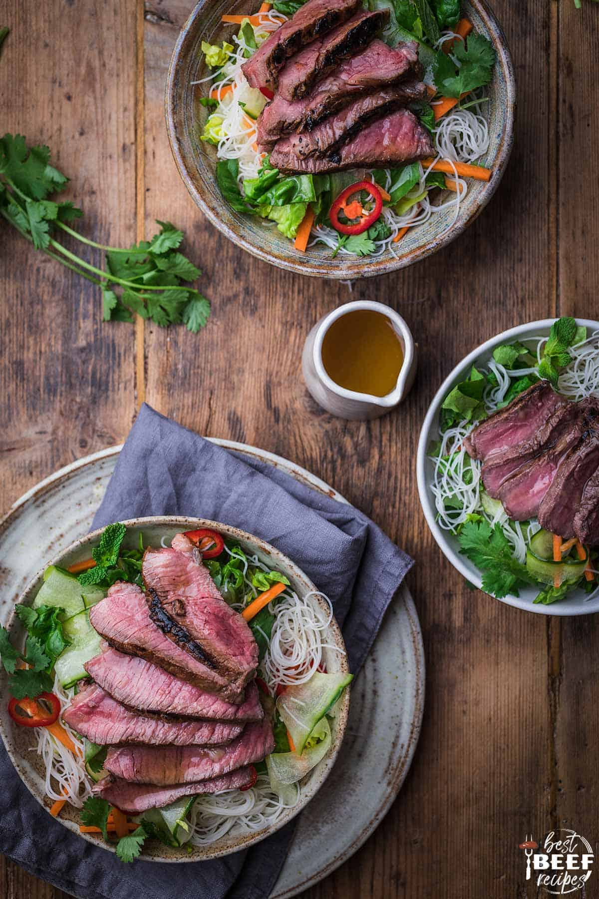 Two large bowls of Vietnamese steak salad and one small bowl