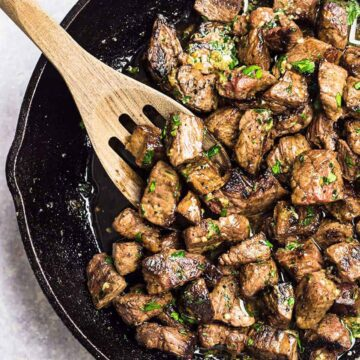 Garlic butter steak bites in a skillet with a wooden slotted spoon
