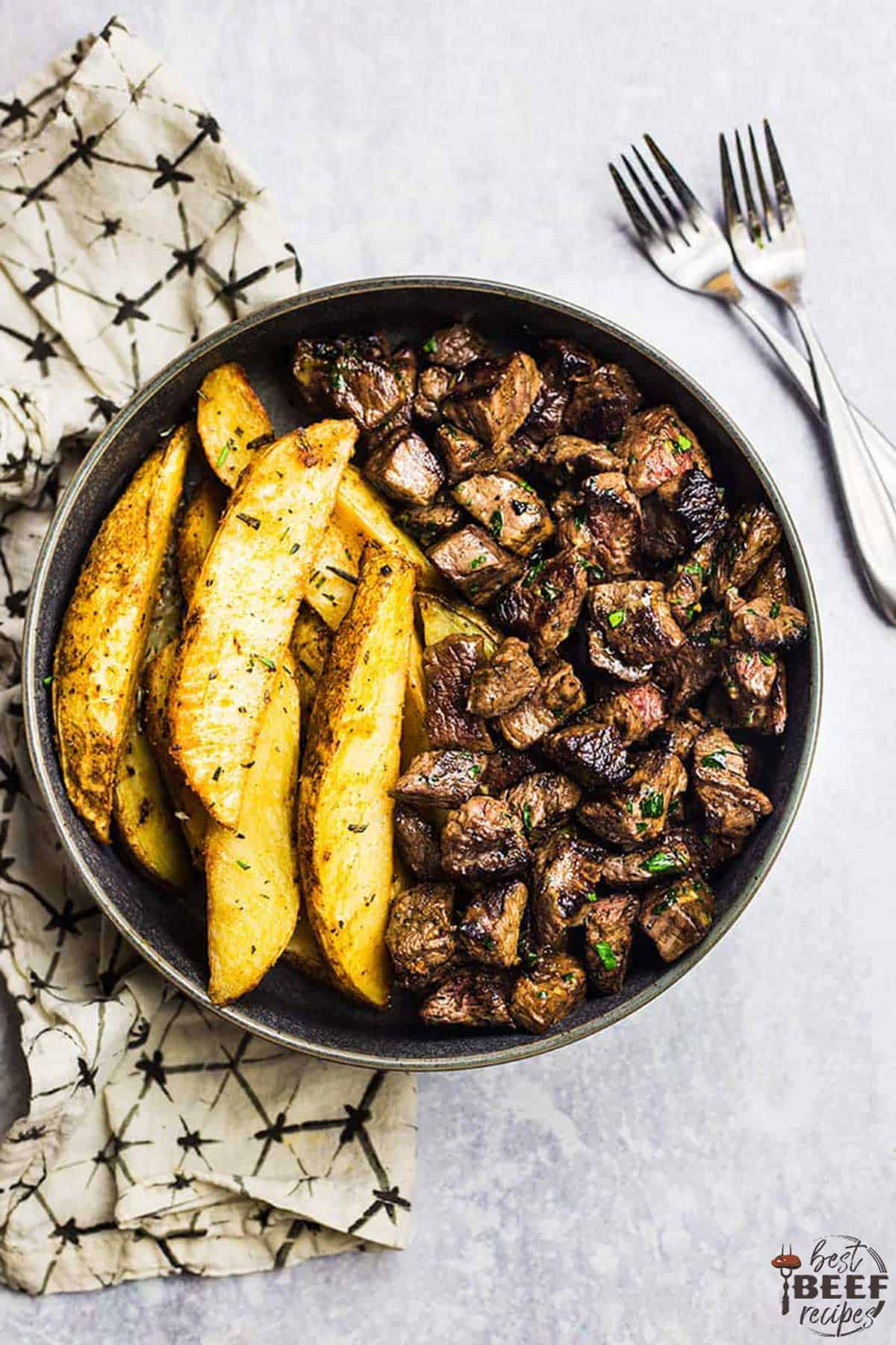Steak bites in a round bowl with potato wedges