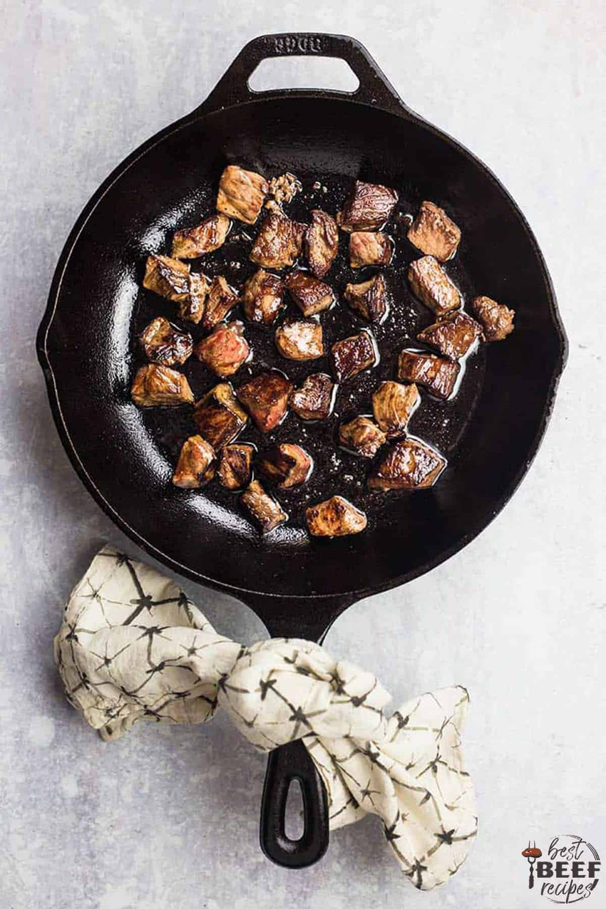 Garlic butter steak bites cooking in a skillet