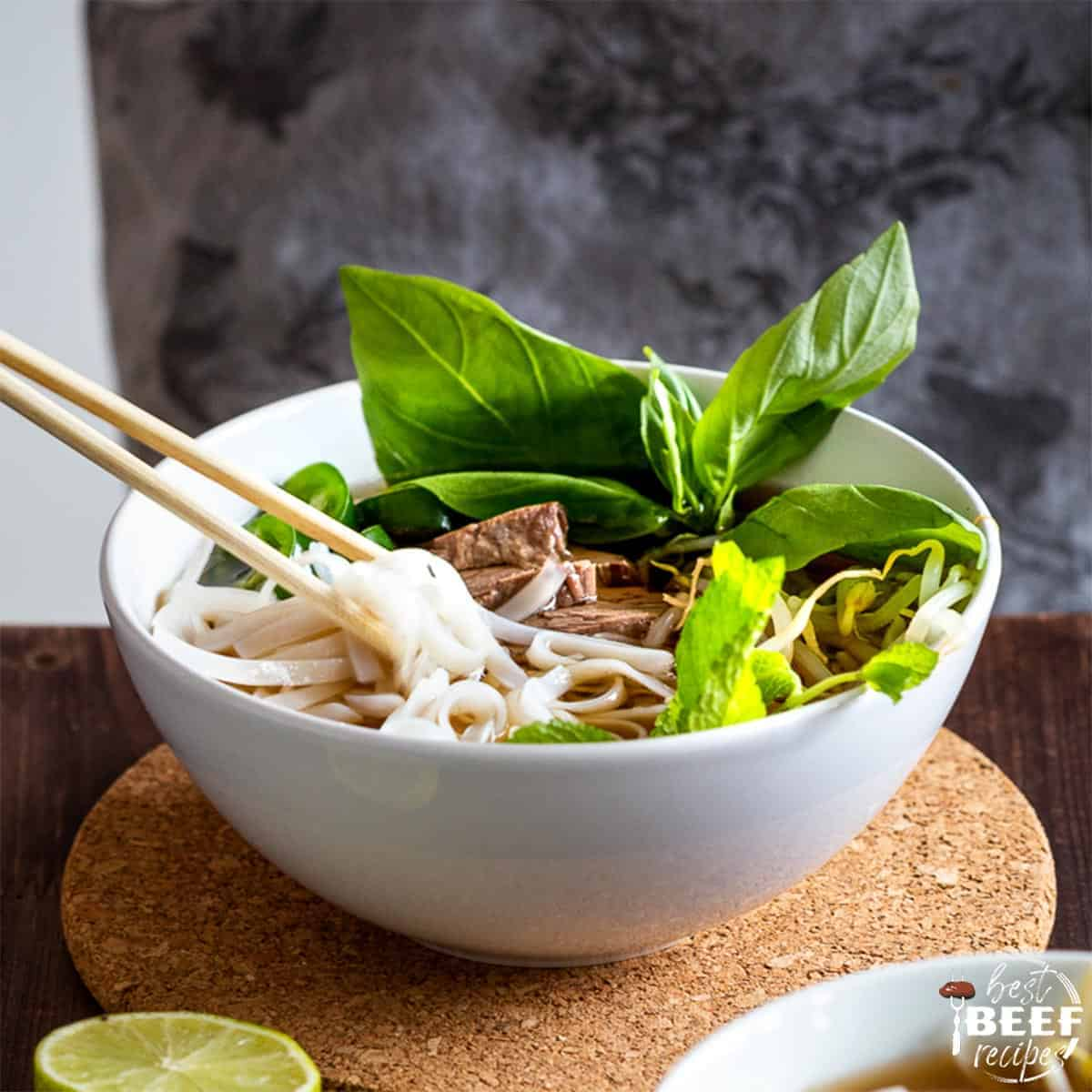 Close up of beef pho in a white bowl with chopsticks