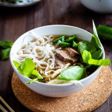 Close up of beef pho in a white bowl