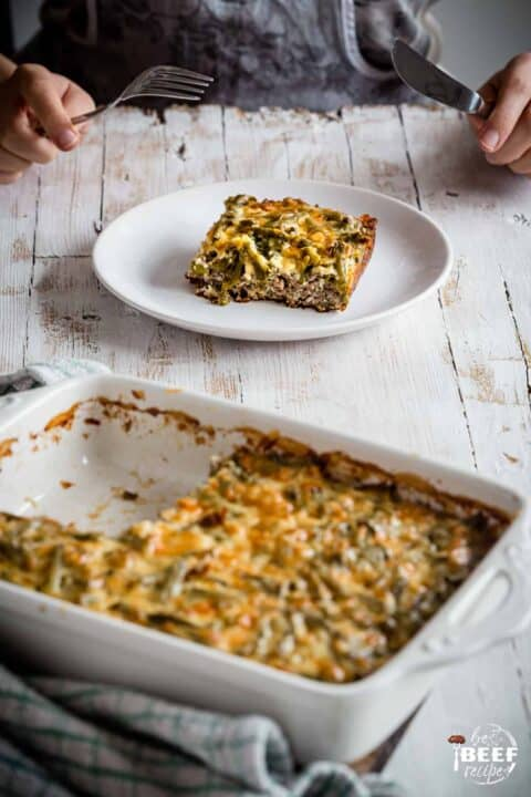 Serving of keto casserole recipe on a plate with a baking dish of hamburger casserole