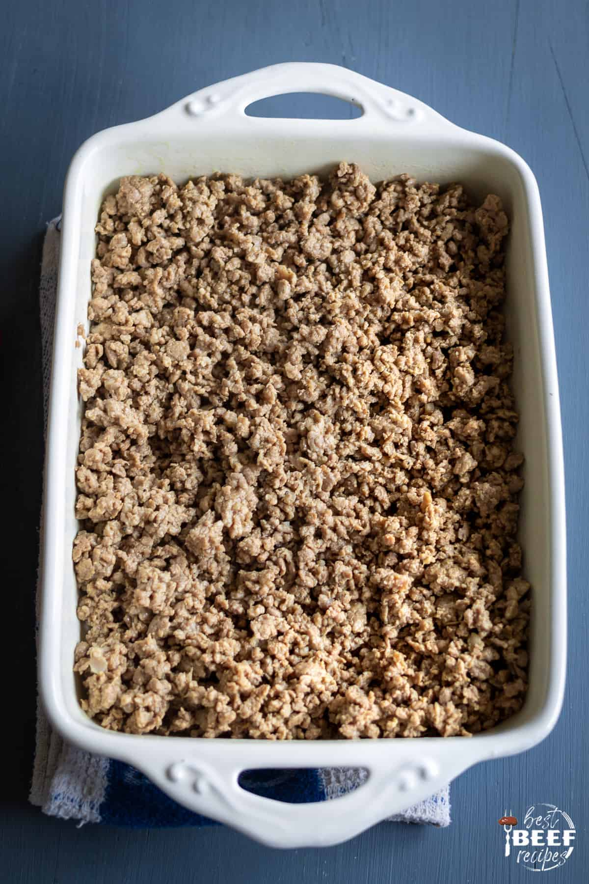 Layering the ground beef in a white baking dish for keto hamburger casserole
