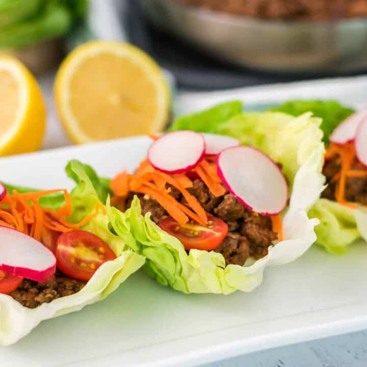 Line of three Portuguese beef lettuce wraps on a white plate