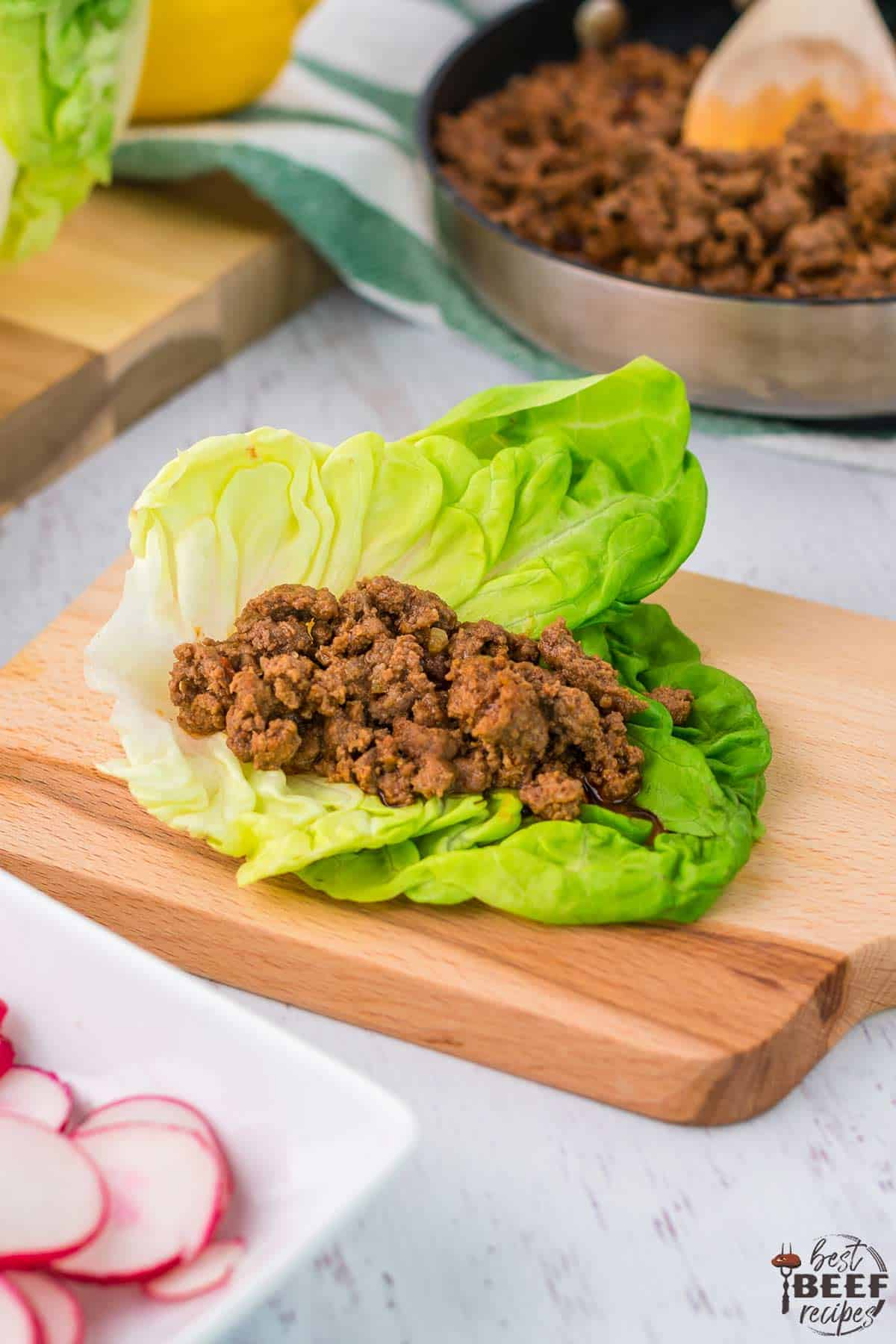 Filled beef lettuce wrap sitting on serving board