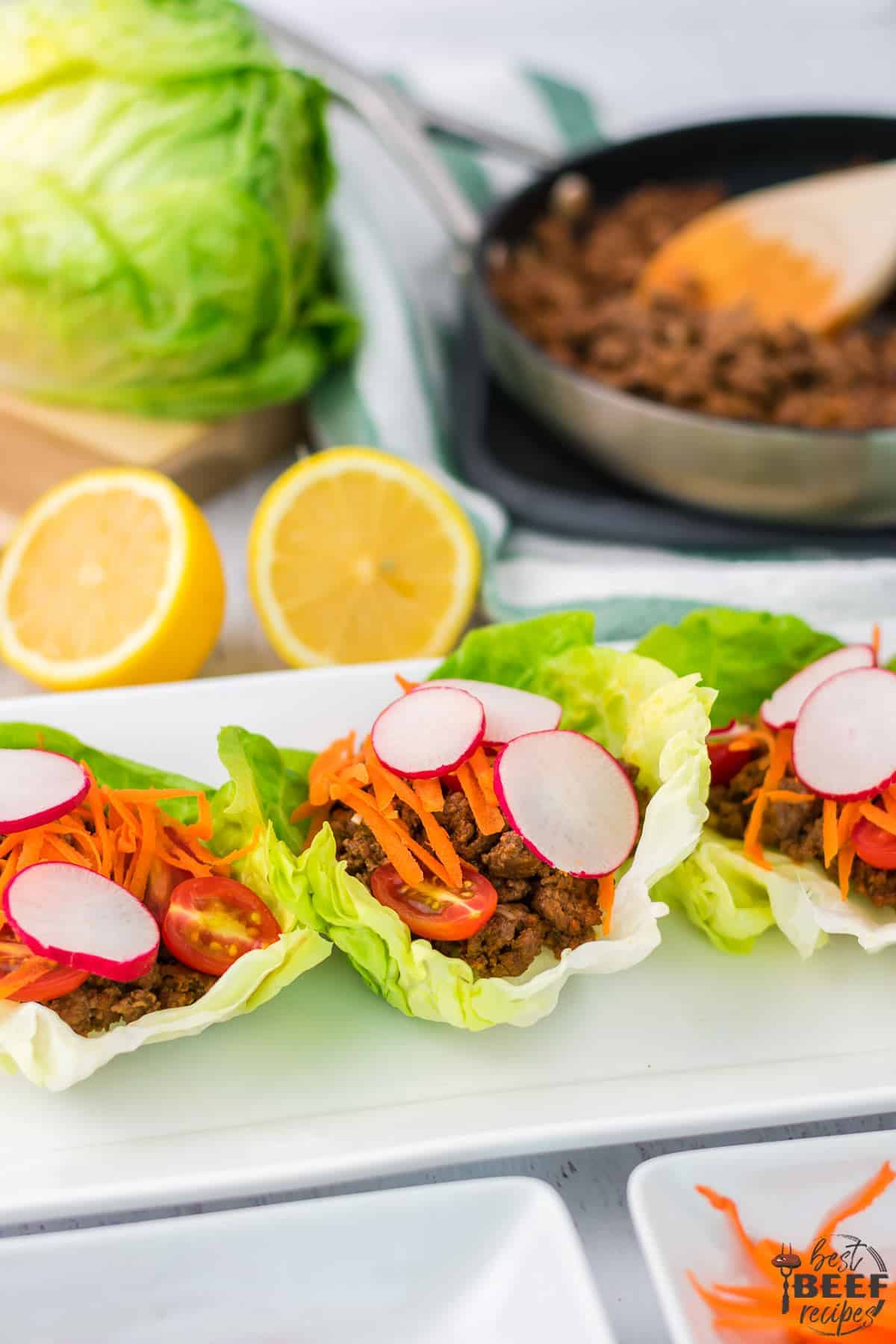 Close up of three beef lettuce wraps on a plate by the skillet of ground beef