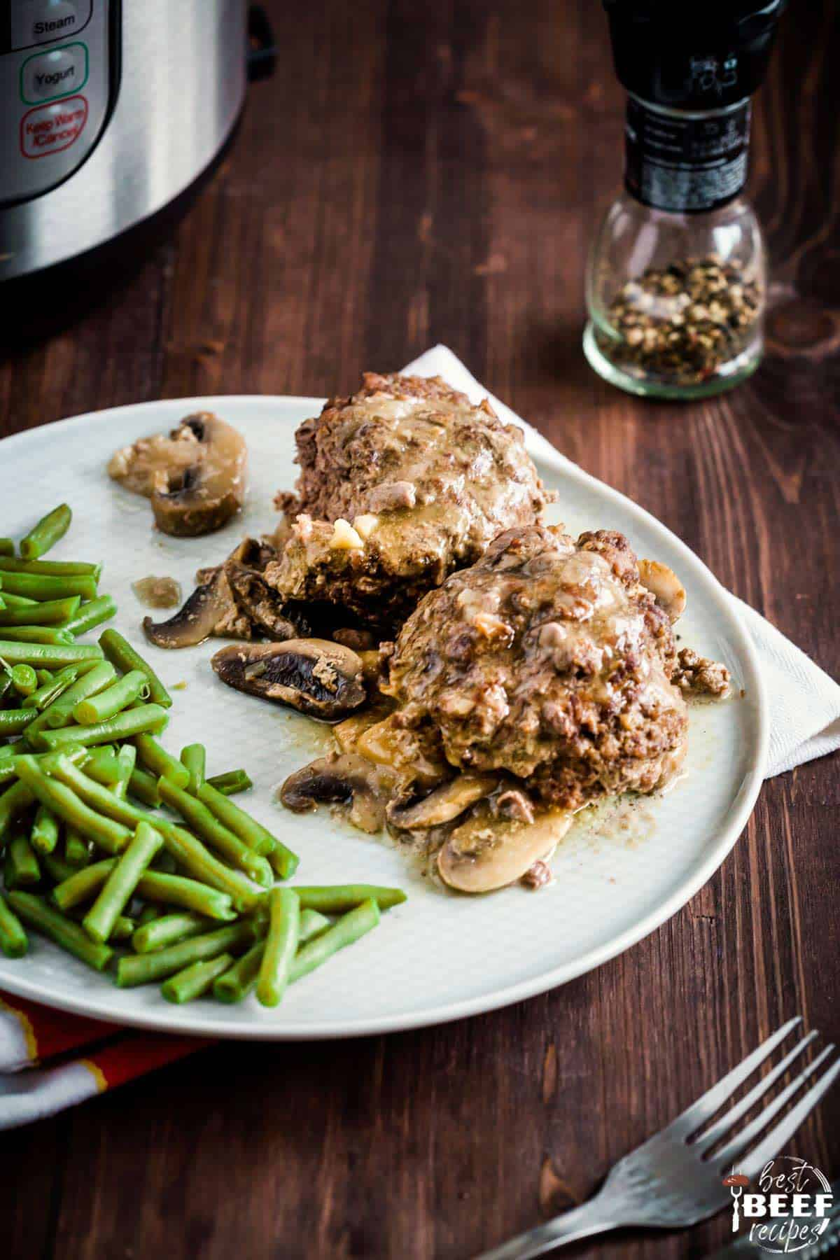 Instant Pot Salisbury Steak Recipe on a plate with green beans and mushroom gravy