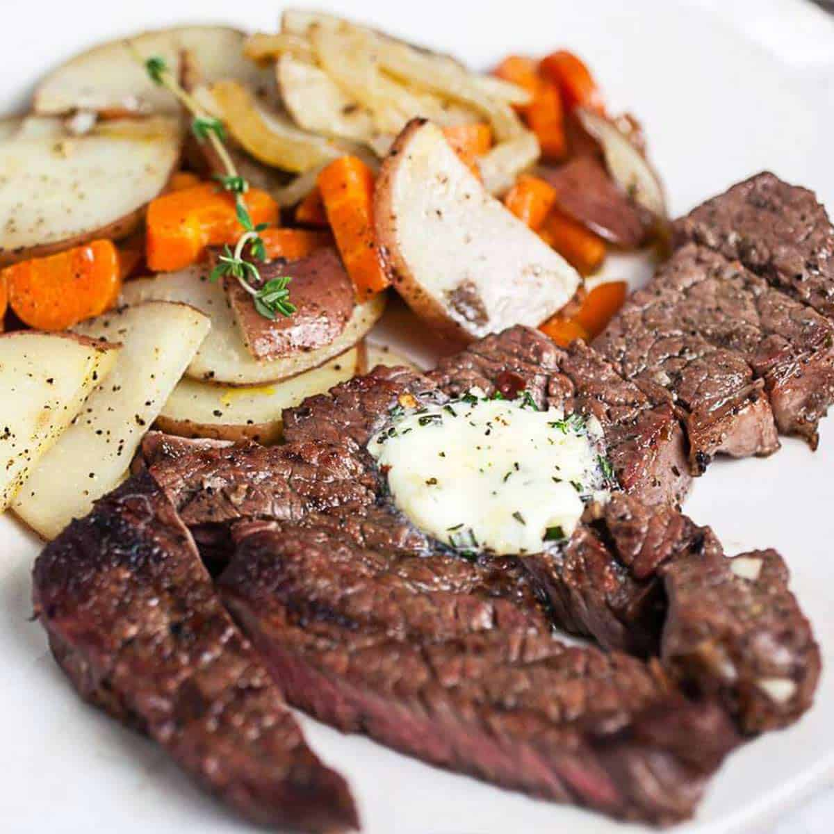 Chuck tender steak with compound butter and potatoes