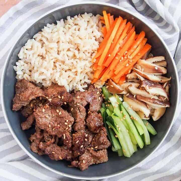 A bowl of Korean beef bulgogi with carrots, cucumbers, mushrooms and rice