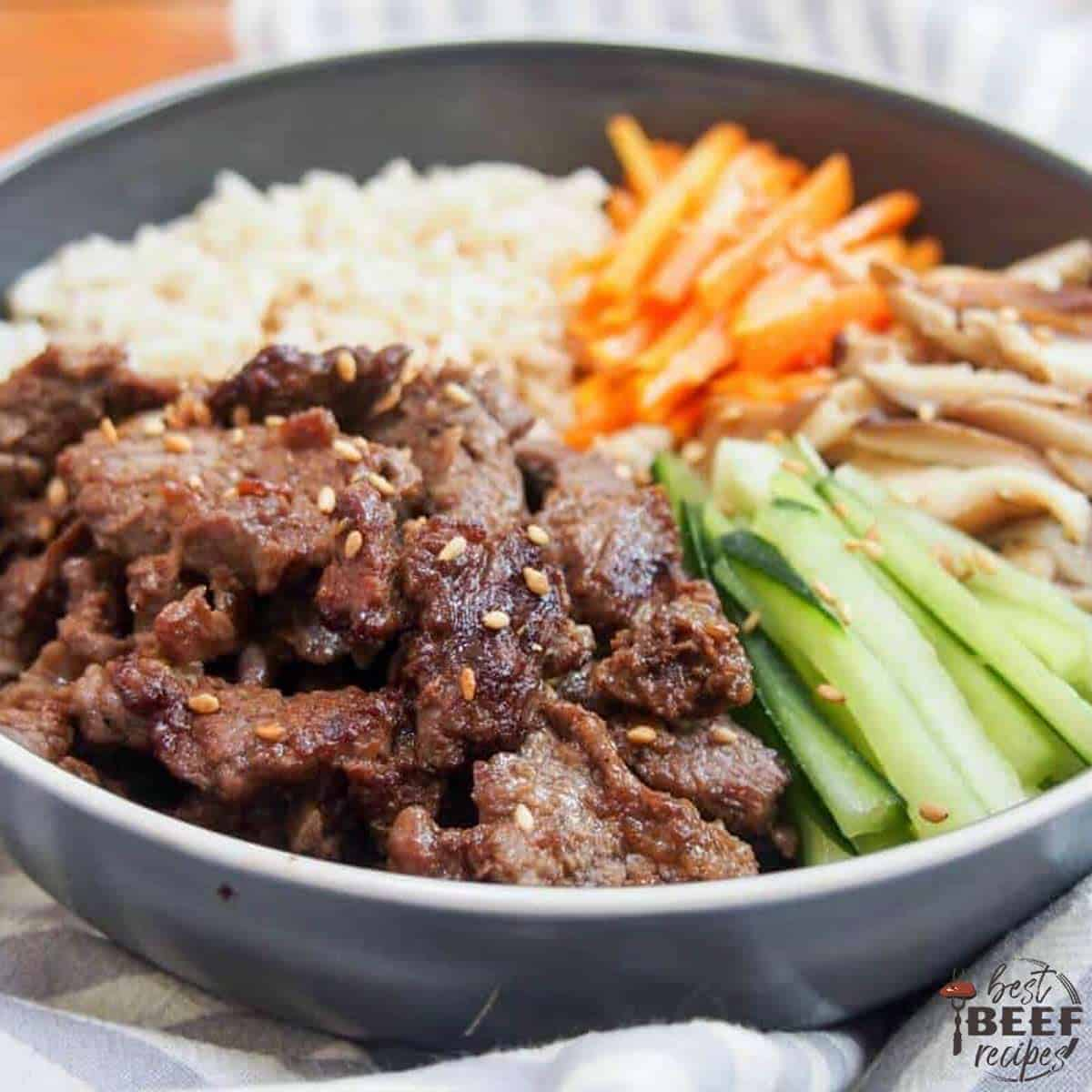 A close up of the Korean beef bowl with sesame seeds, vegetables, and rice, in a black bowl