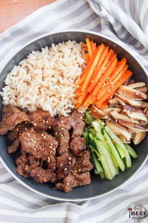 Korean beef bulgogi bowl recipe overhead shot with sliced cucumbers, carrots, and shiitake mushrooms over rice
