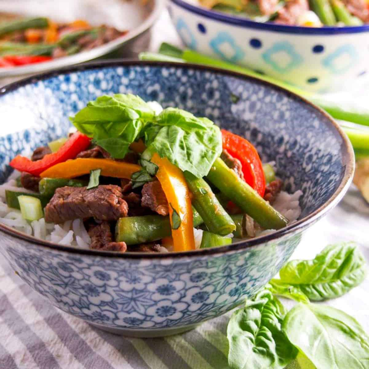 Pepper steak stir fry recipe in a blue and white bowl with fresh basil on top