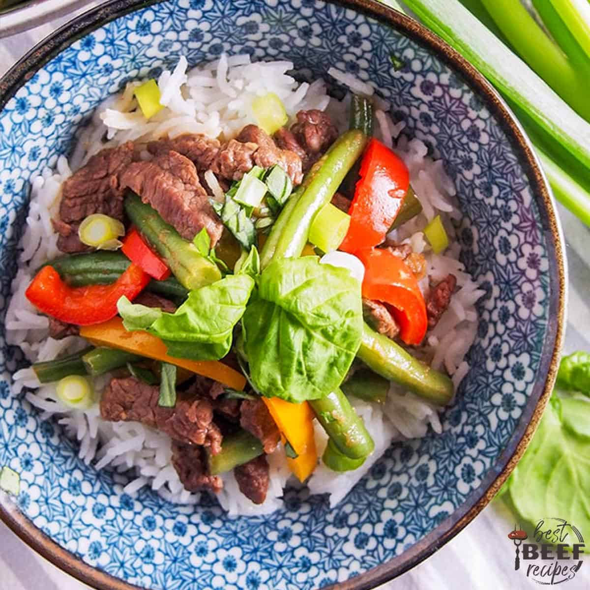 Pepper steak stir fry recipe in a blue and white bowl over white rice