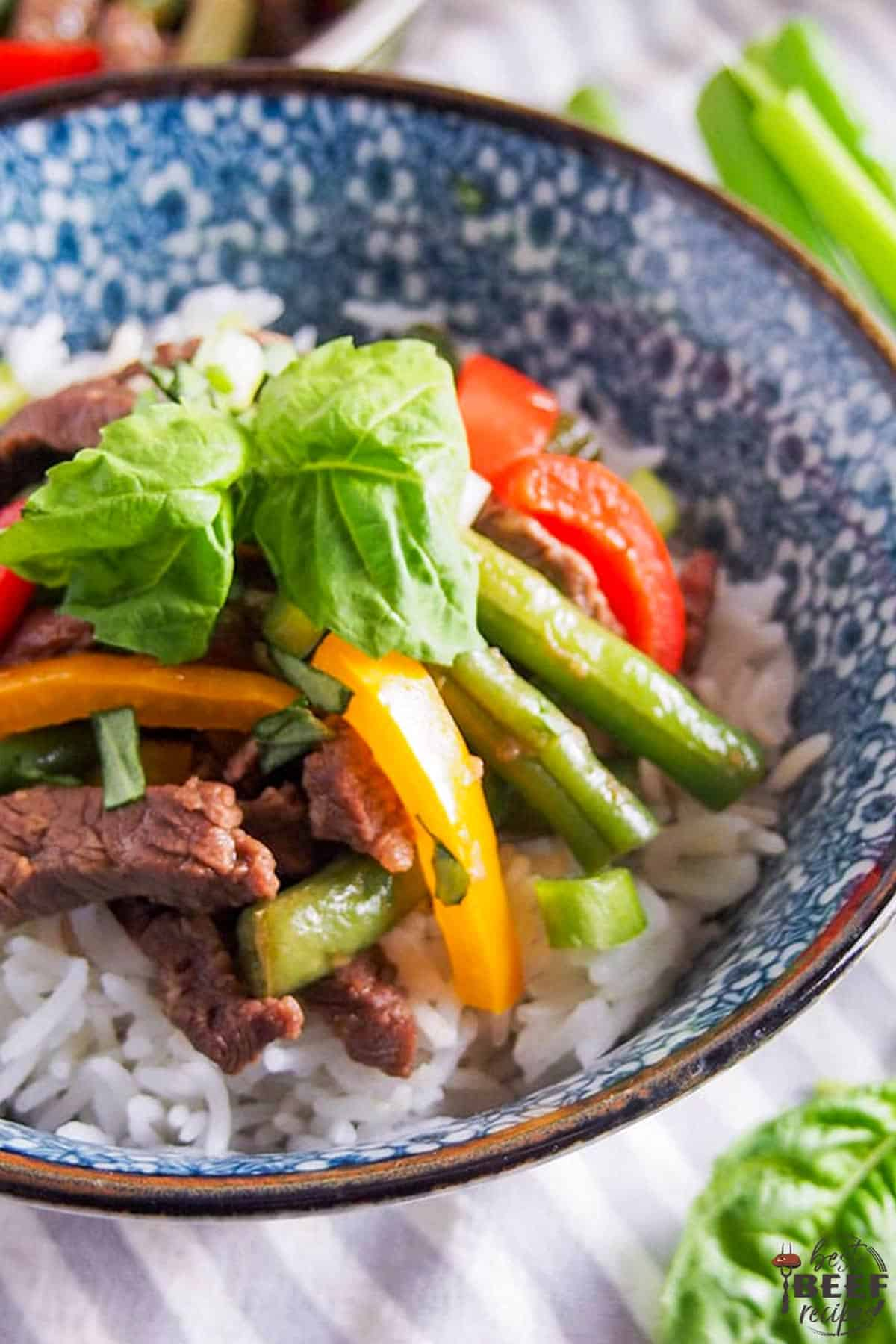 Close up of pepper steak stir fry recipe in a blue and white bowl over rice