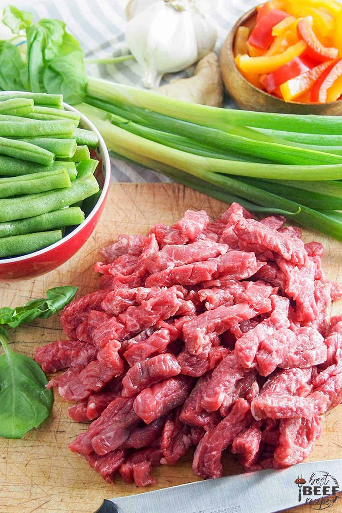 Sliced flank steak on a cutting board with trimmed green beans and green onions