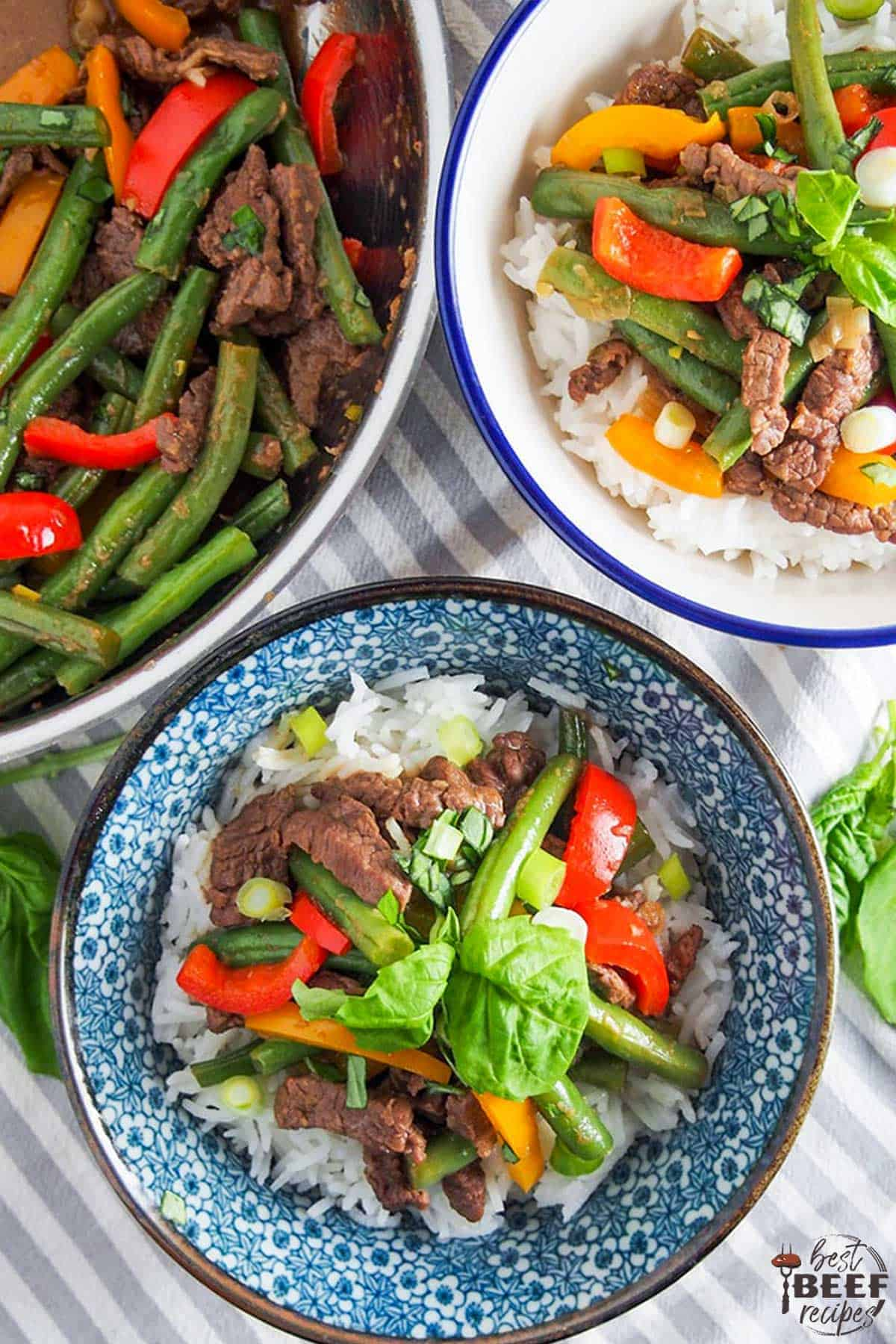 Two bowls of Asian beef stir fry with a pot of stir fry leftover
