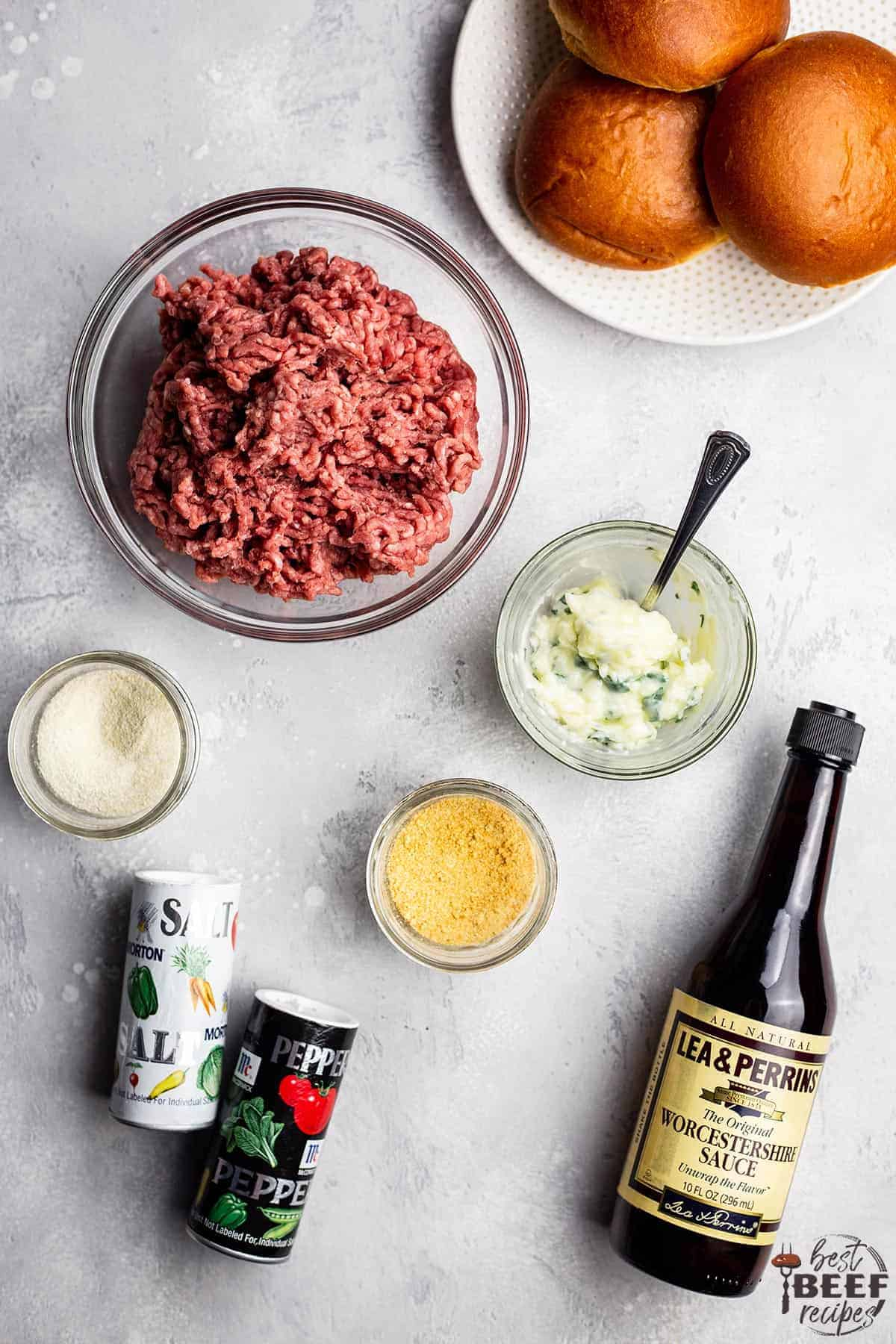 Ingredients to make air fryer burger recipe laid out on a white surface, including ground beef, garlic butter spread, burger seasonings, buns, and a bottle of Worcestershire sauce