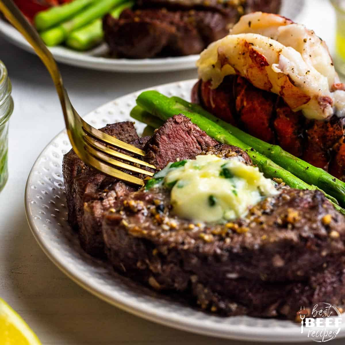 air fried steak on a plate with a fork, asparagus and lobster