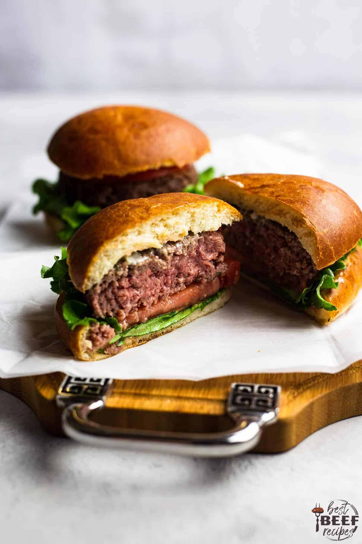A garlic butter burger cut in half to show the medium-rare middle