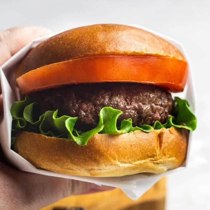 Holding up a garlic butter burger with parchment paper wrapped around it made using air fryer burger recipe