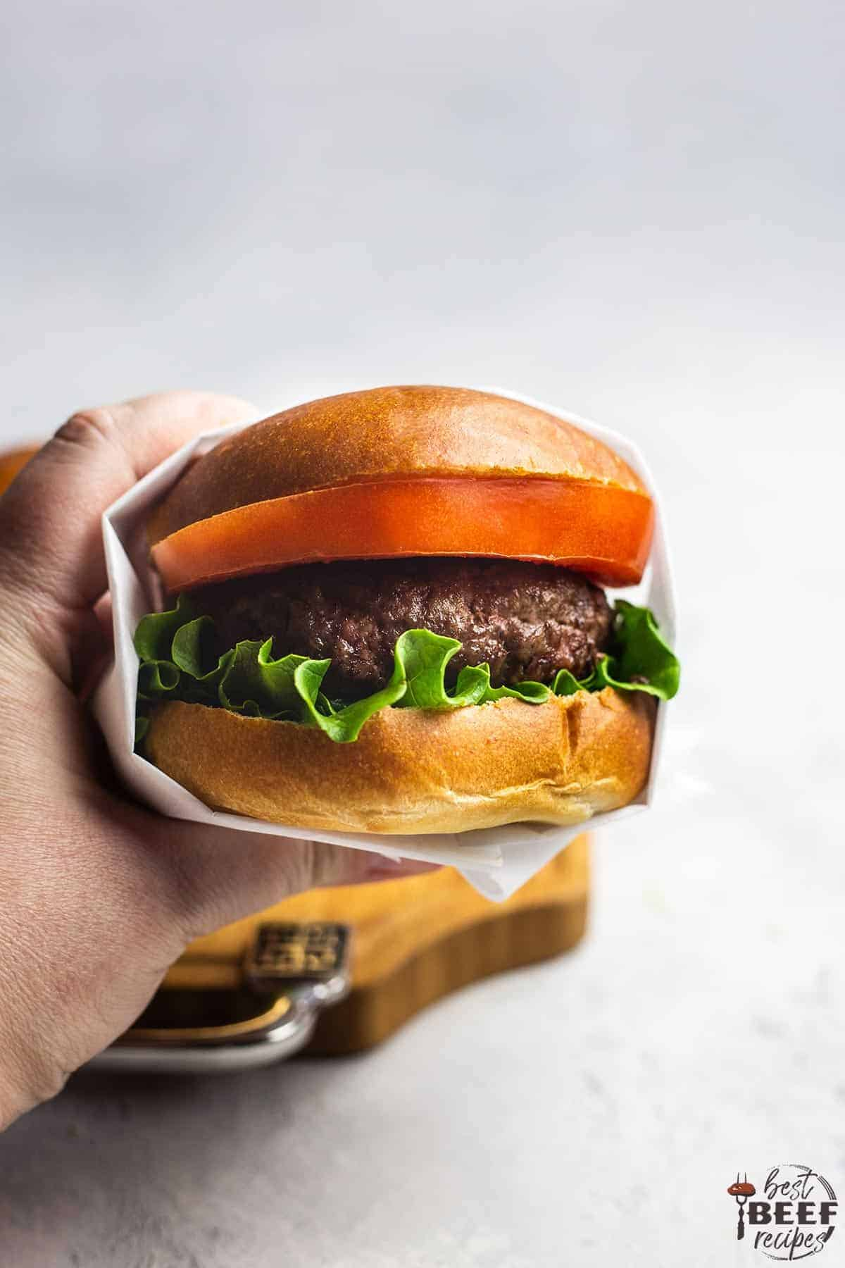 Holding up a garlic butter burger that's wrapped with white paper