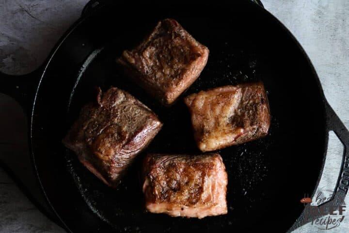 Beef ribs searing in cast iron pan