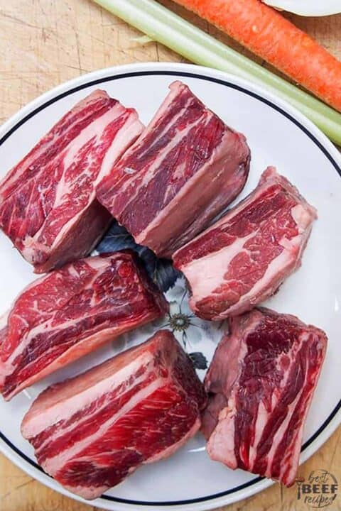 Uncooked beef short ribs on a plate next to celery and carrots on a cutting board for slow cooker beef ribs recipe