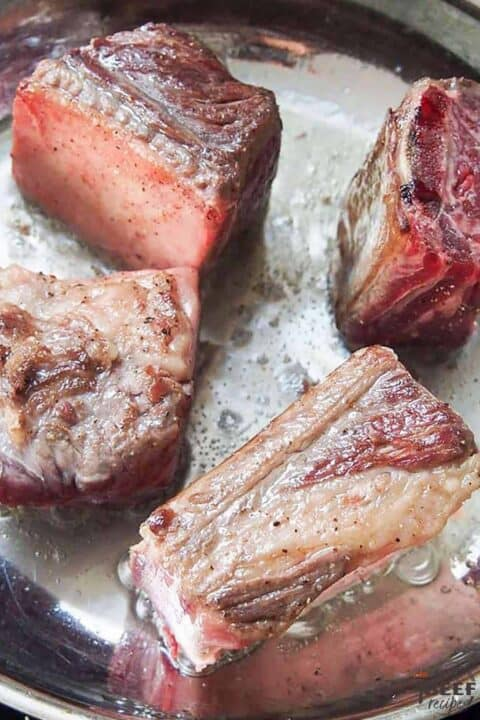 Searing the beef short ribs in a skillet for slow cooker beef ribs