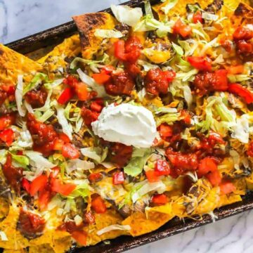 Sheet pan nachos with steak slices, sour cream, tomatoes, and lettuce