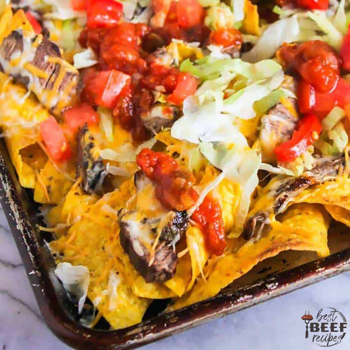 Close up of steak nachos in a sheet pan with slices of steak, lettuce and chopped tomatoes