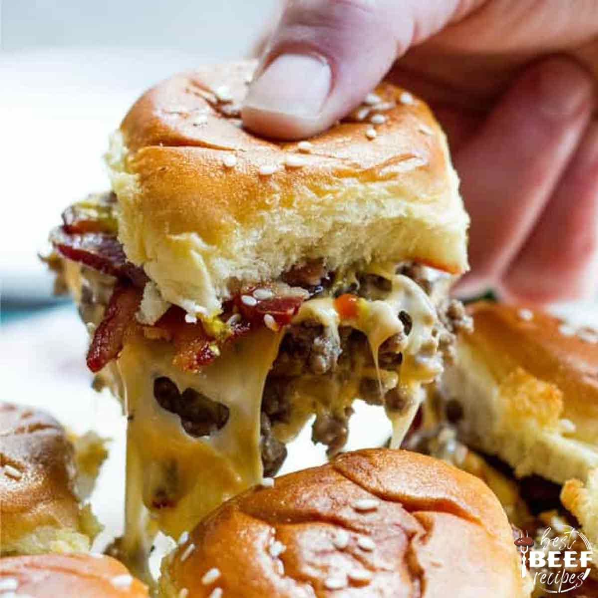 Lifting up a mini cheeseburger from the other cheeseburger sliders
