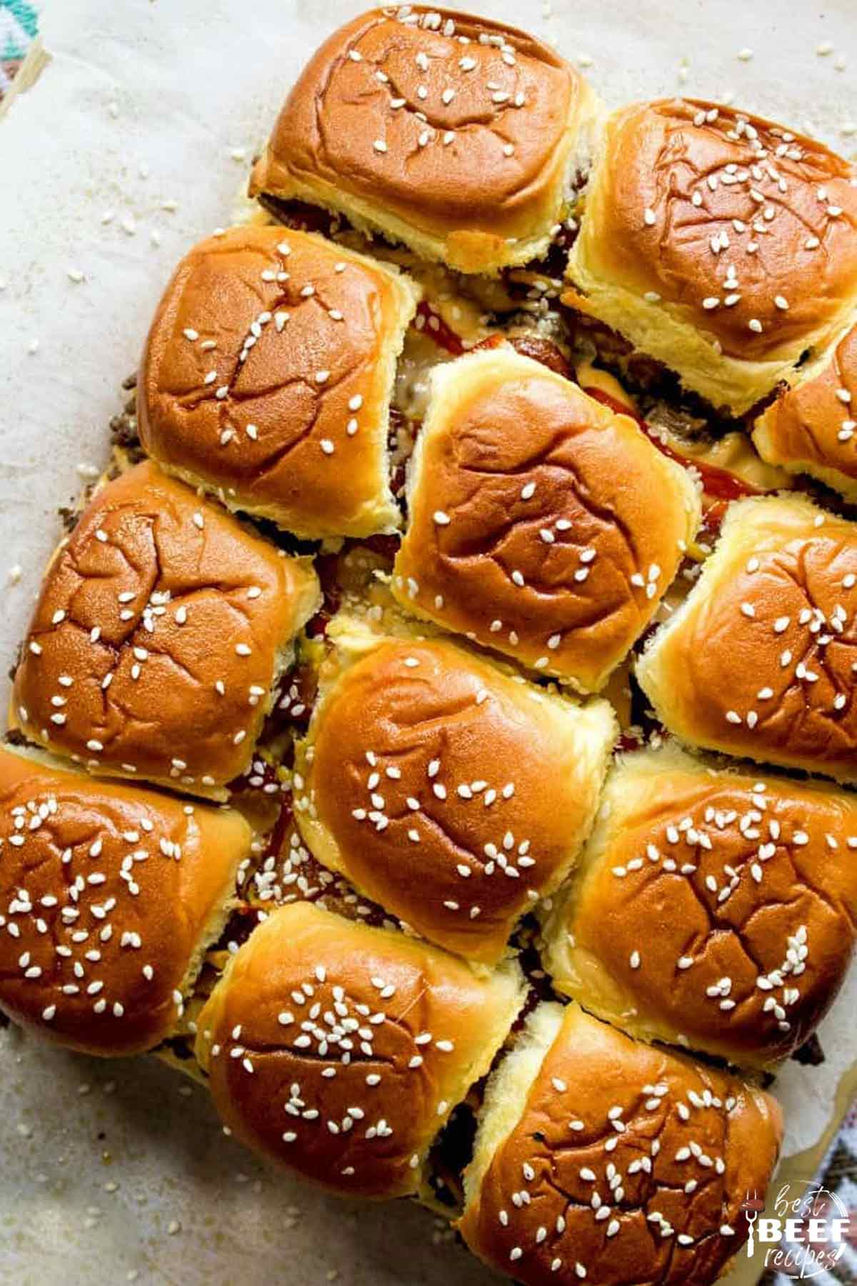 12 bacon cheeseburger sliders on Hawaiian rolls topped with sesame seeds