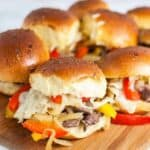 Philly cheesesteak sliders on a wooden board up close