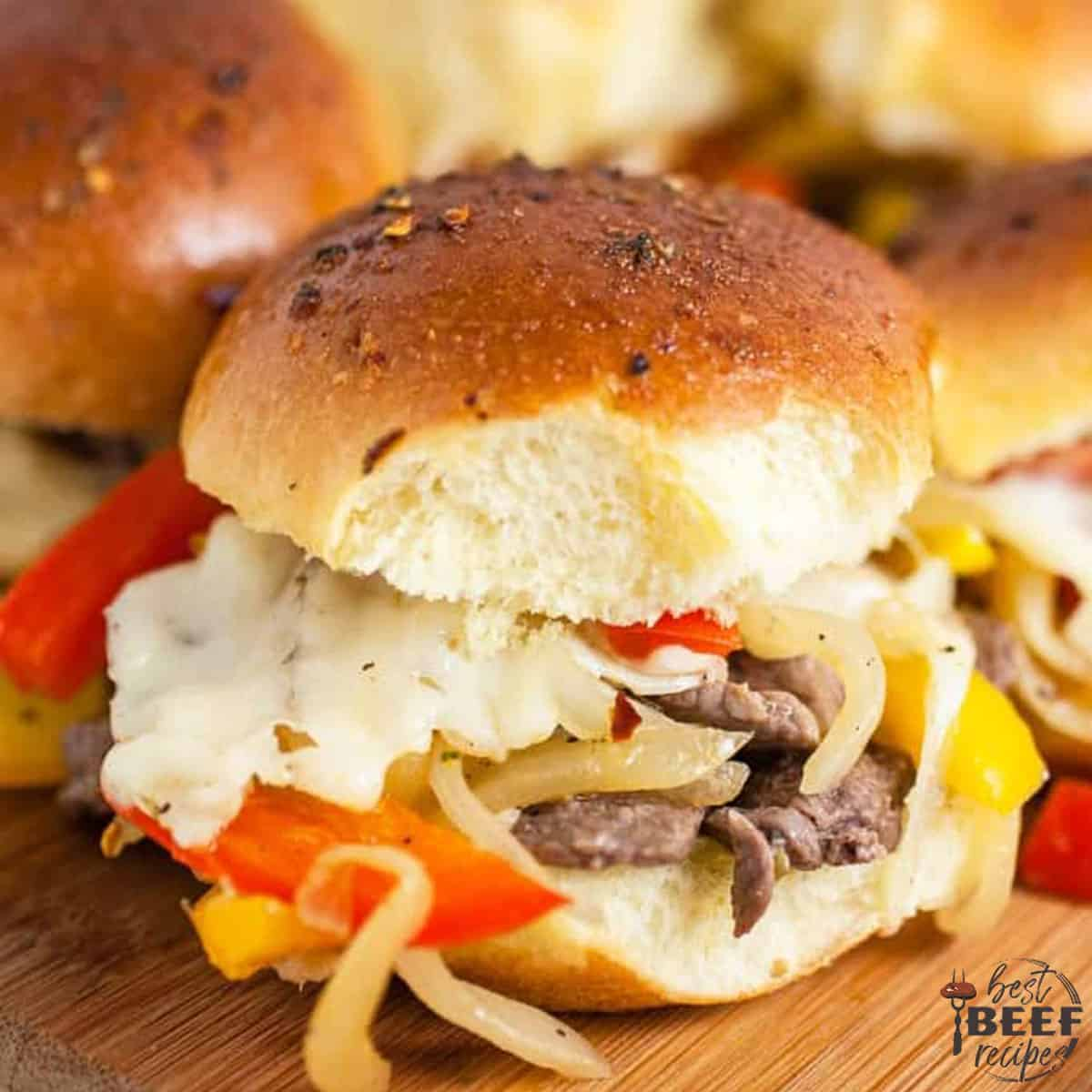 Close up of Philly cheesesteak sliders with peppers and onions