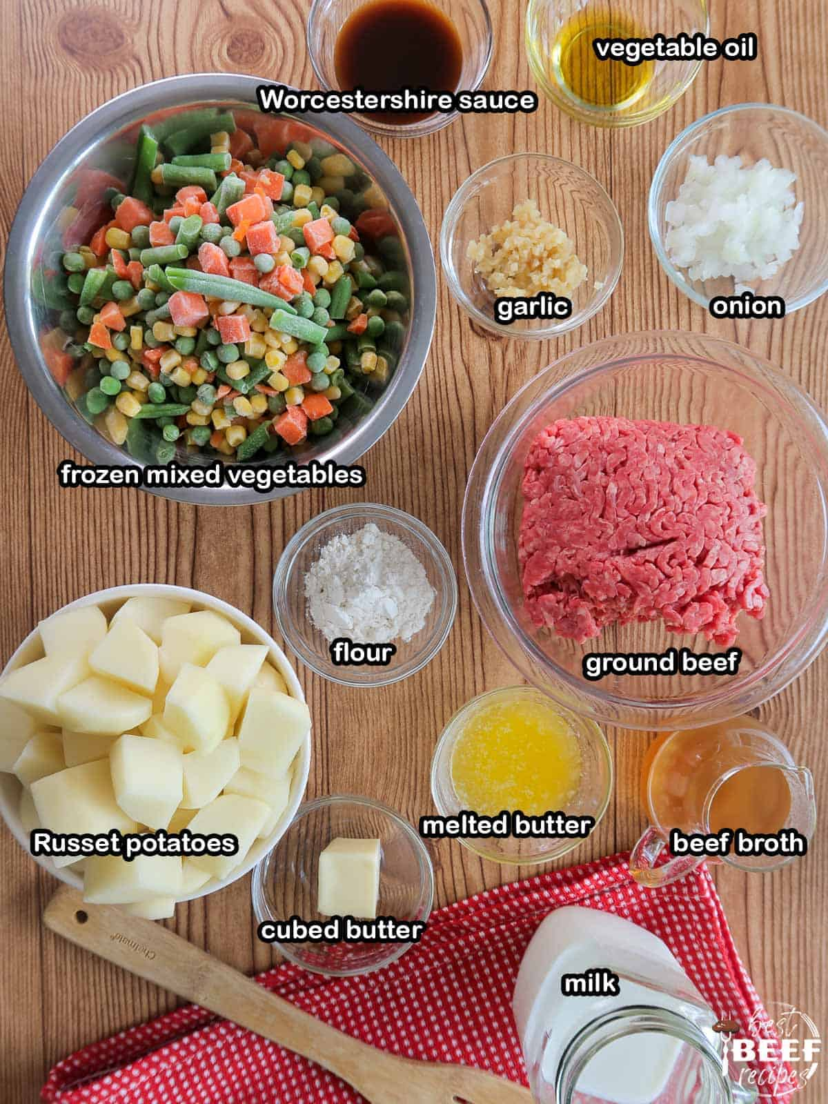 Ingredients to make Instant Pot Shepherd's Pie labeled on a brown wood surface
