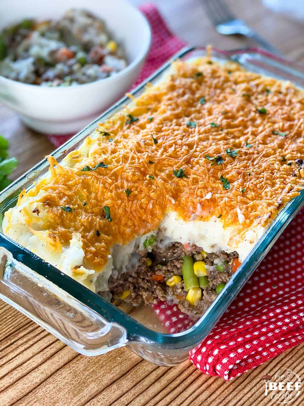 Shepherd's Pie in a casserole dish with a portion served in a white bowl