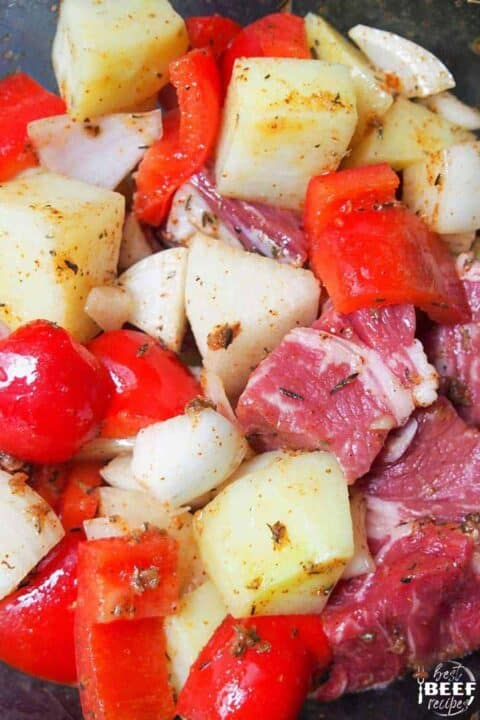 Diced steak, potatoes, peppers, and onions up close coated in oil
