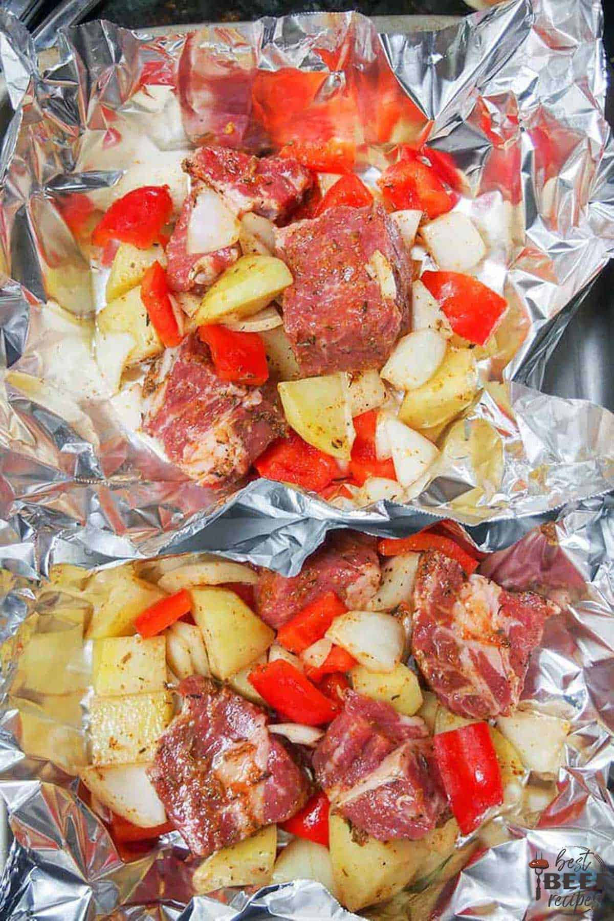 Diced steak, peppers, potatoes, and onions in foil, ready to wrap into steak foil packs