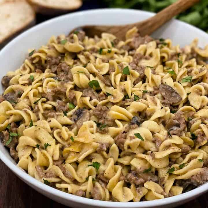 Close up of instant pot beef stroganoff in a white dish with a wooden spoon