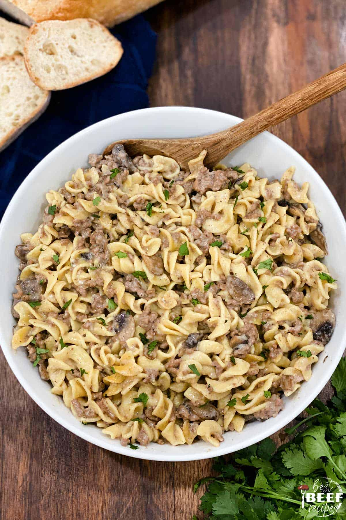 Overhead view of instant pot ground beef stroganoff in a white dish with a wooden spoon and bread to the side
