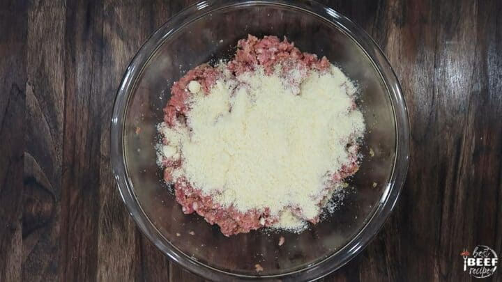 Parmesan over ground beef in a glass bowl
