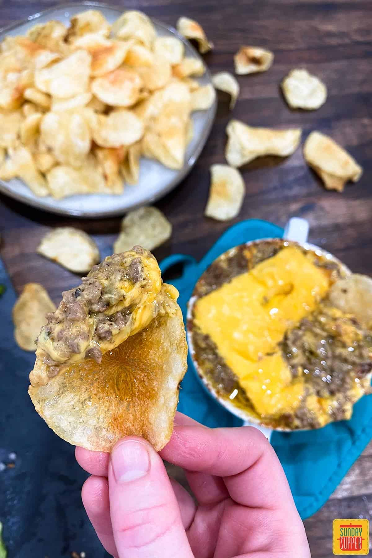Dipping a chip into the instant pot philly cheese steak dip with cheese on top