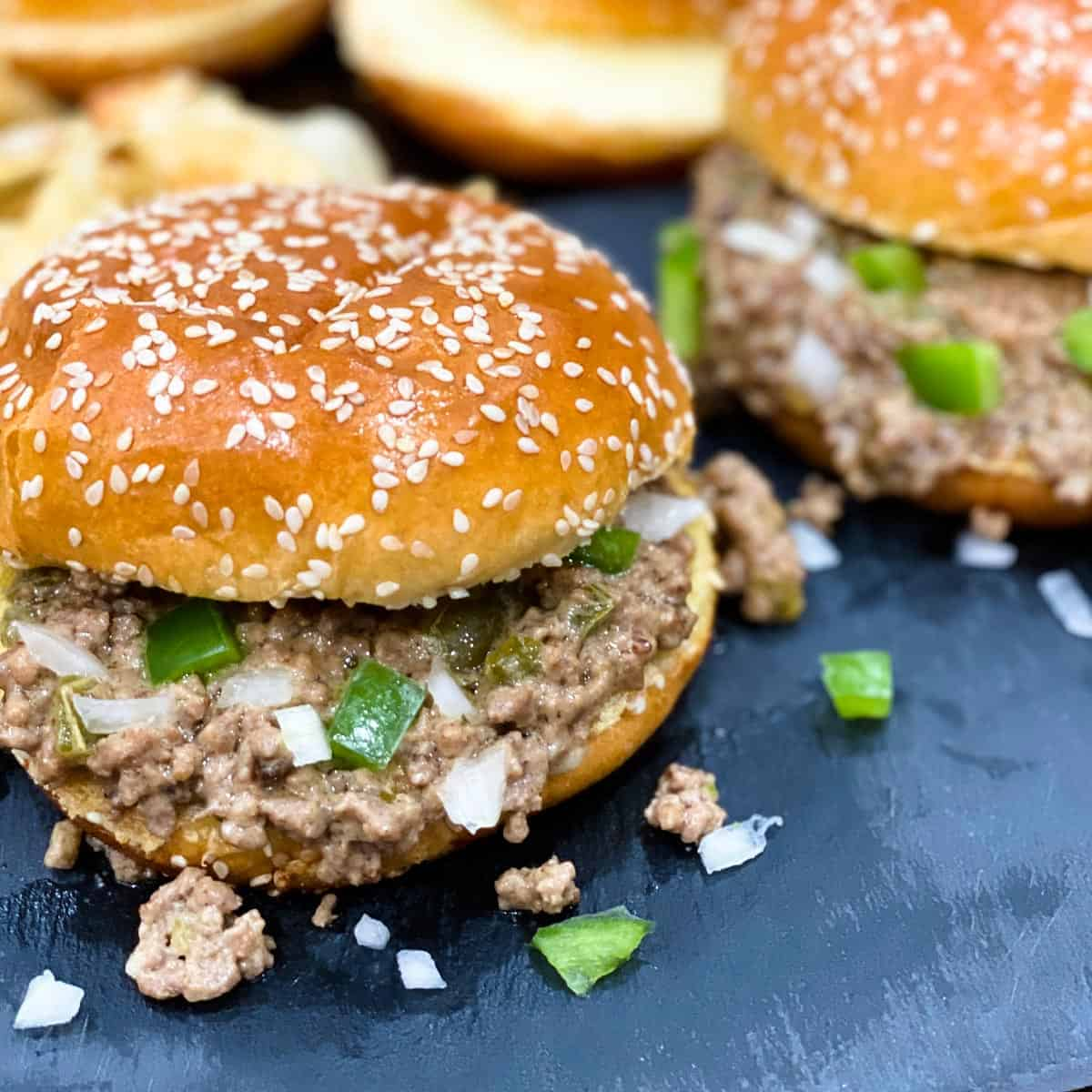 Close up of two philly cheesesteak sloppy joes with green bell peppers and onions on a black surface