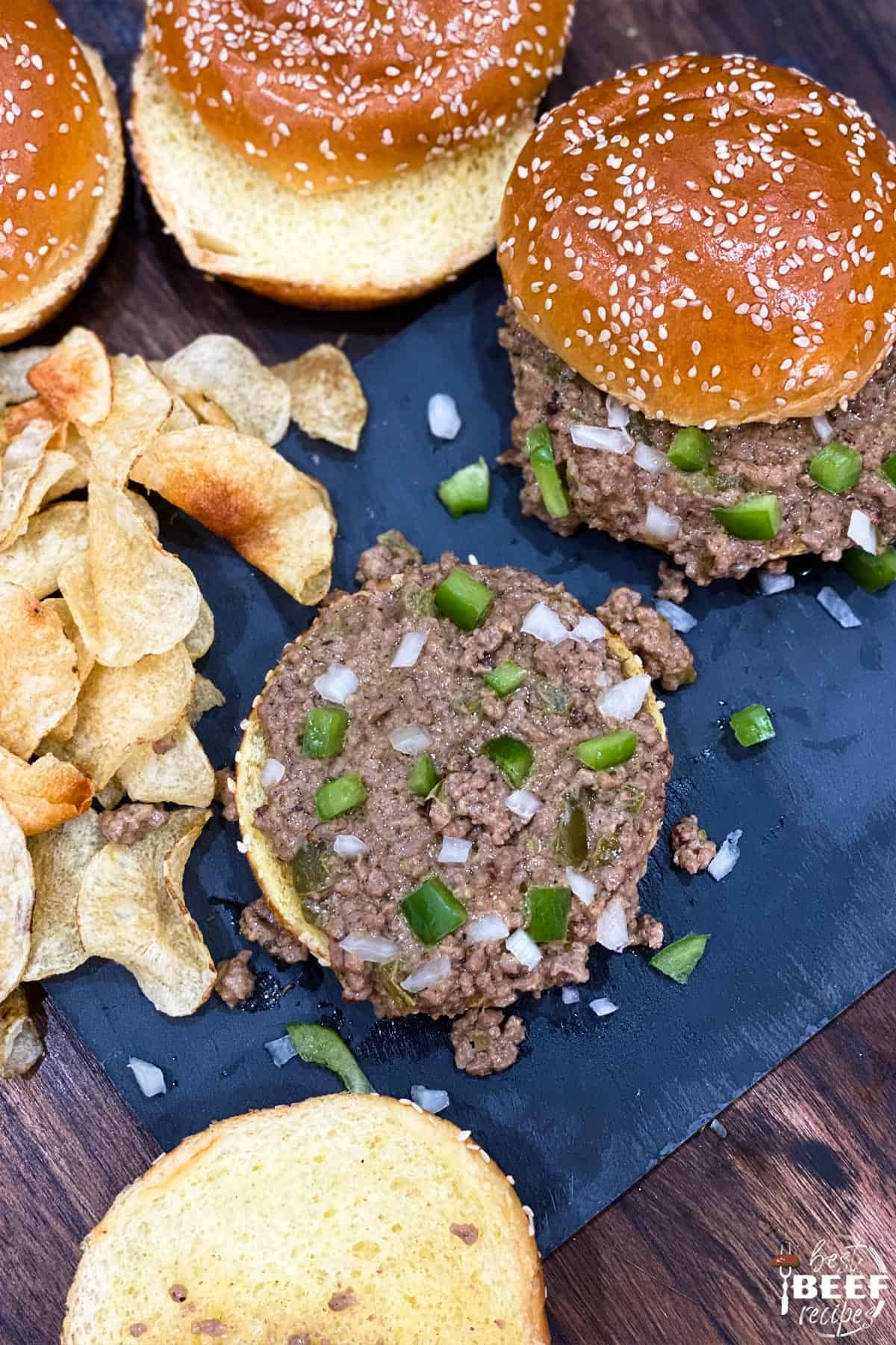 Top-down view of Instant pot philly cheesesteak sloppy joes next to potato chips on a black surface