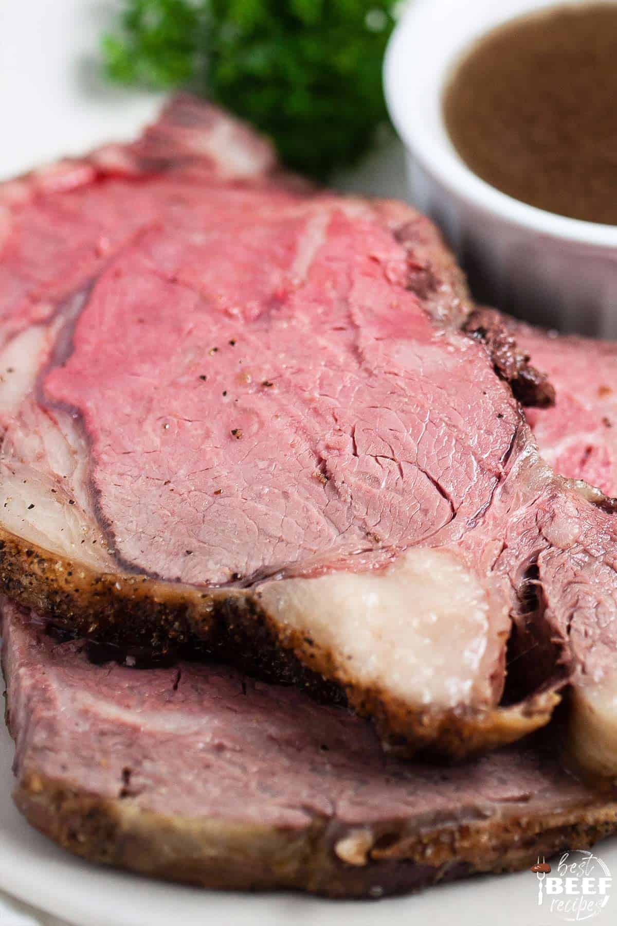 Close up of two slices of prime rib on a white plate
